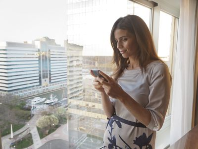 a woman checking her phone in a hotel room