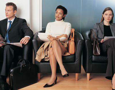 Three Business Executives Sitting in Armchairs Waiting for an Interview