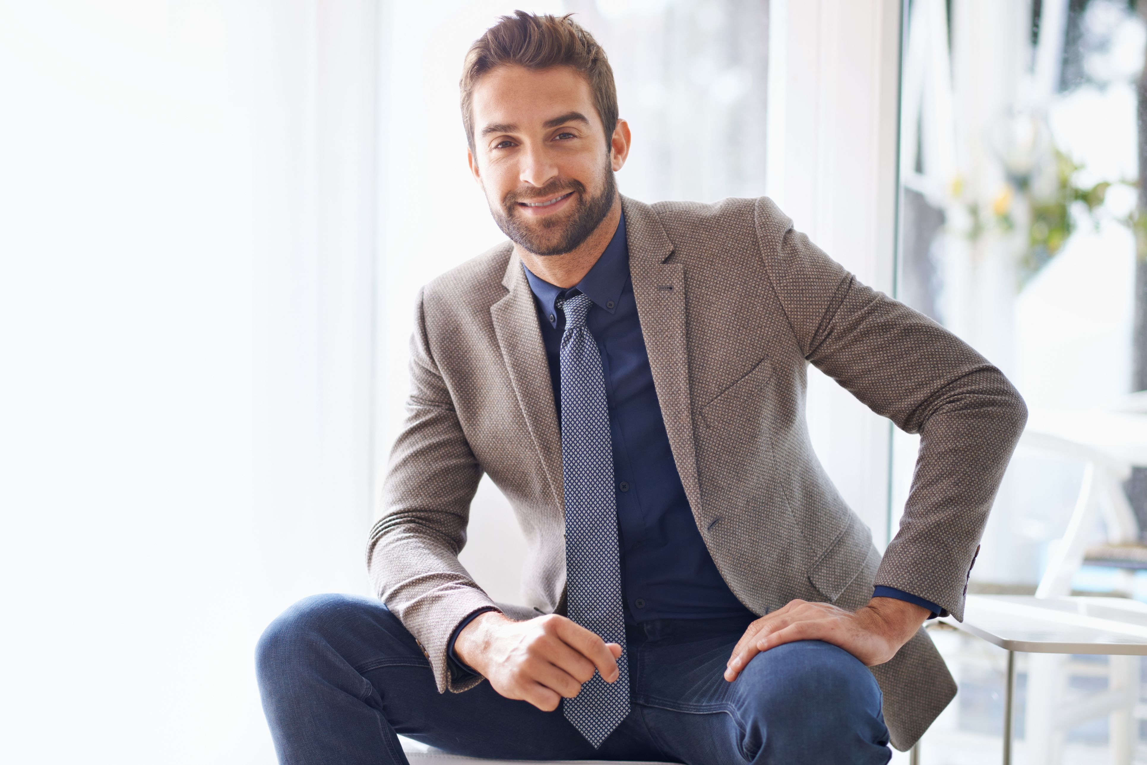 Young man wearing a shirt, tie, blazer, and jeans.