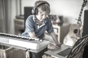 Child making music on laptop and keyboard