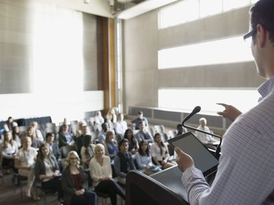 Professor with digital tablet speaking to students auditorium