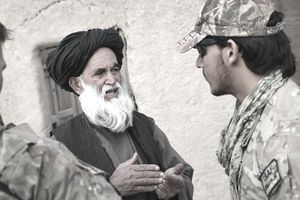 KANDAHAR, AFGHANISTAN - MARCH 05: An Afghan interpreter with the U.S. Army's 4th squadron 2d Cavalry Regiment helps to question a villager during a joint patrol with soldiers from the Afghan National Army (ANA) March 5, 2014 near Kandahar, Afghanistan.