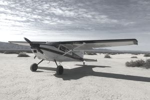 Private owner Cessna 180 used by a bush pilot parked by a remote runway