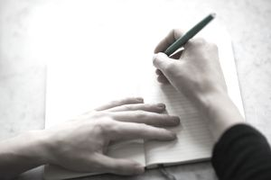 Woman's hand holding a pen preparing to write a story on a blank page in a notebook.