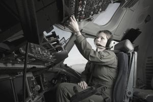 An Air Force pilot adjusts controls in a cockpit