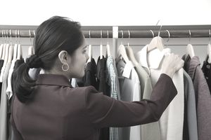 Young woman looking at sweater on clothes rack, rear view