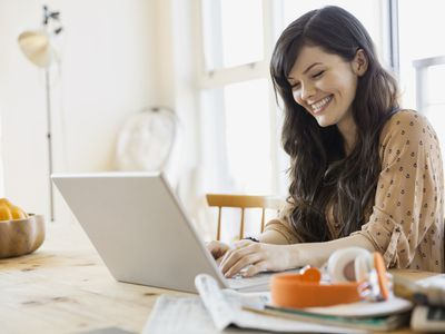 Woman working from home on a flexible schedule using her laptop at her kitchen table.