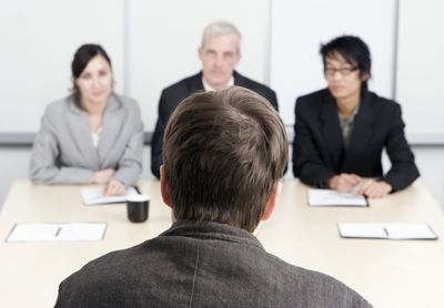A man being interviewed by three people answering questions about his period of unemployment.