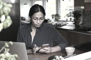 Woman using phone and laptop