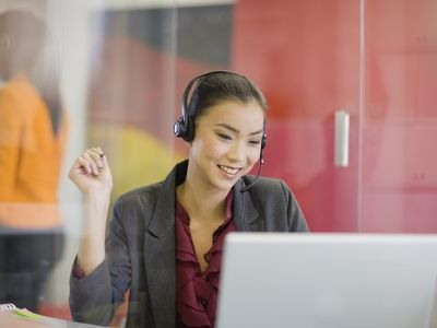 A telemarketer using a headset and laptop talking to a customer.