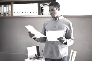 Man reading papers with concerned expression