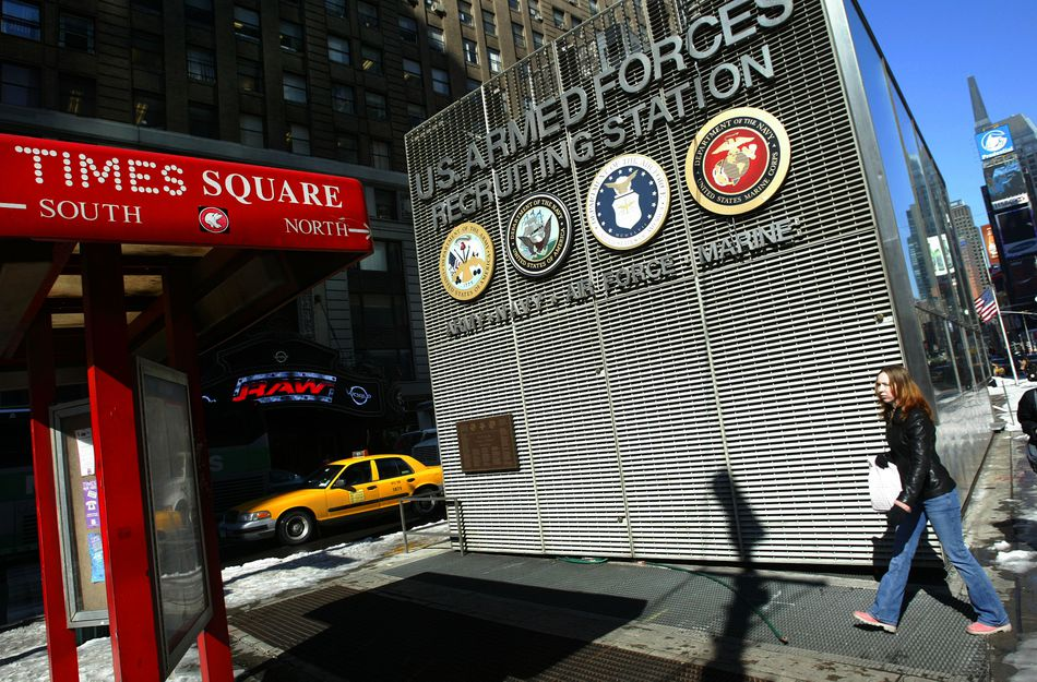 A young woman walking past the Times Square Armed Forces Recruitment Center sign.