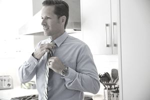 man in dress shirt putting on tie in kitchen
