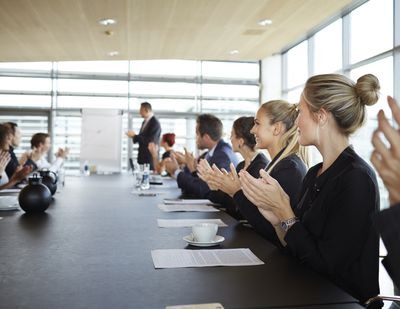 Coworkers sitting around conference table with a facilitator leading