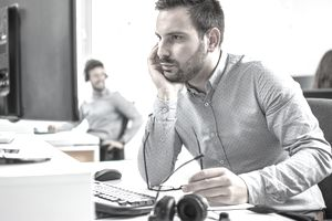 Man looking at computer screen and keeping his eyeglasses while sitting at his working place in office.