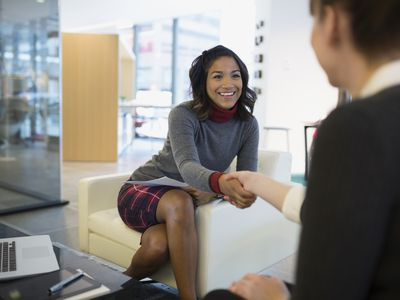 Woman getting job offer, shaking hands with a prospective employer.
