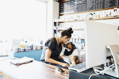 Small business pet store and grooming service petting dog while writing business plan