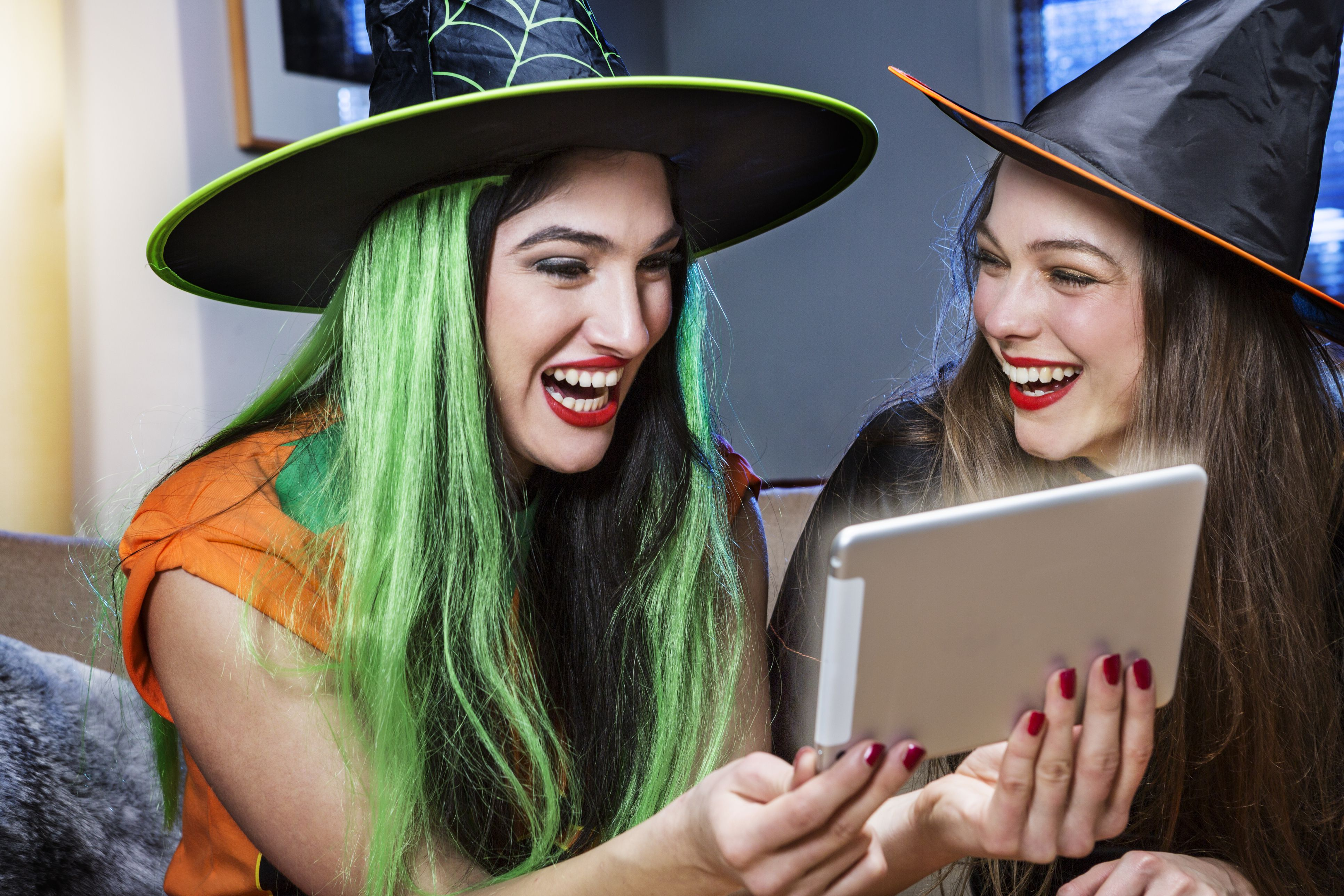 Two Halloween witches looking at an ipad at the Halloween office party.