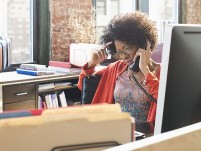 An unhappy worker who may hate her job talking on the office phone