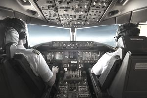 Rear View Of Pilots Sitting In Cockpit