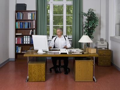 An Internal Affairs Investigator sitting at a desk researching on a computer