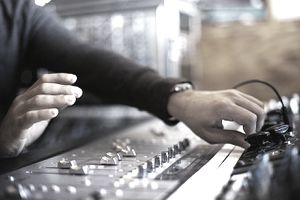 Closeup of man's hands working audio mixing board