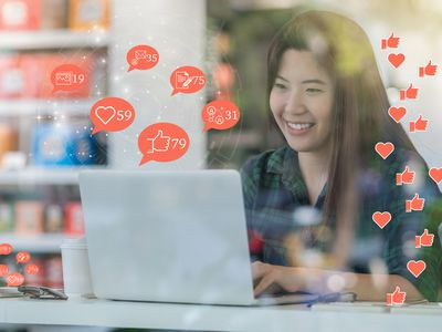 Social media concept, Asian woman hand using laptop to check social network application with number of Like, Love, comment, people and fovorite icon at desk beside glass in coffee shop