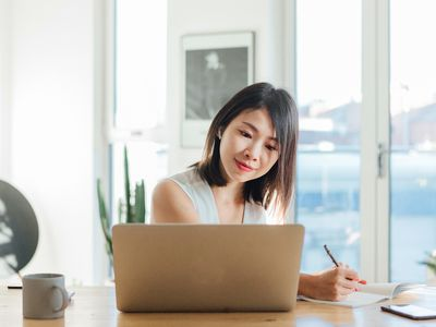 Young woman taking notes while having a video conference using laptop at home