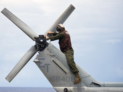 A Marine conducts maintenance on the tail of an UH-1N Huey helicopter.