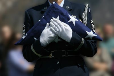 Soldier holding a folded American flag during a military Funeral for active duty death of a military serviceman