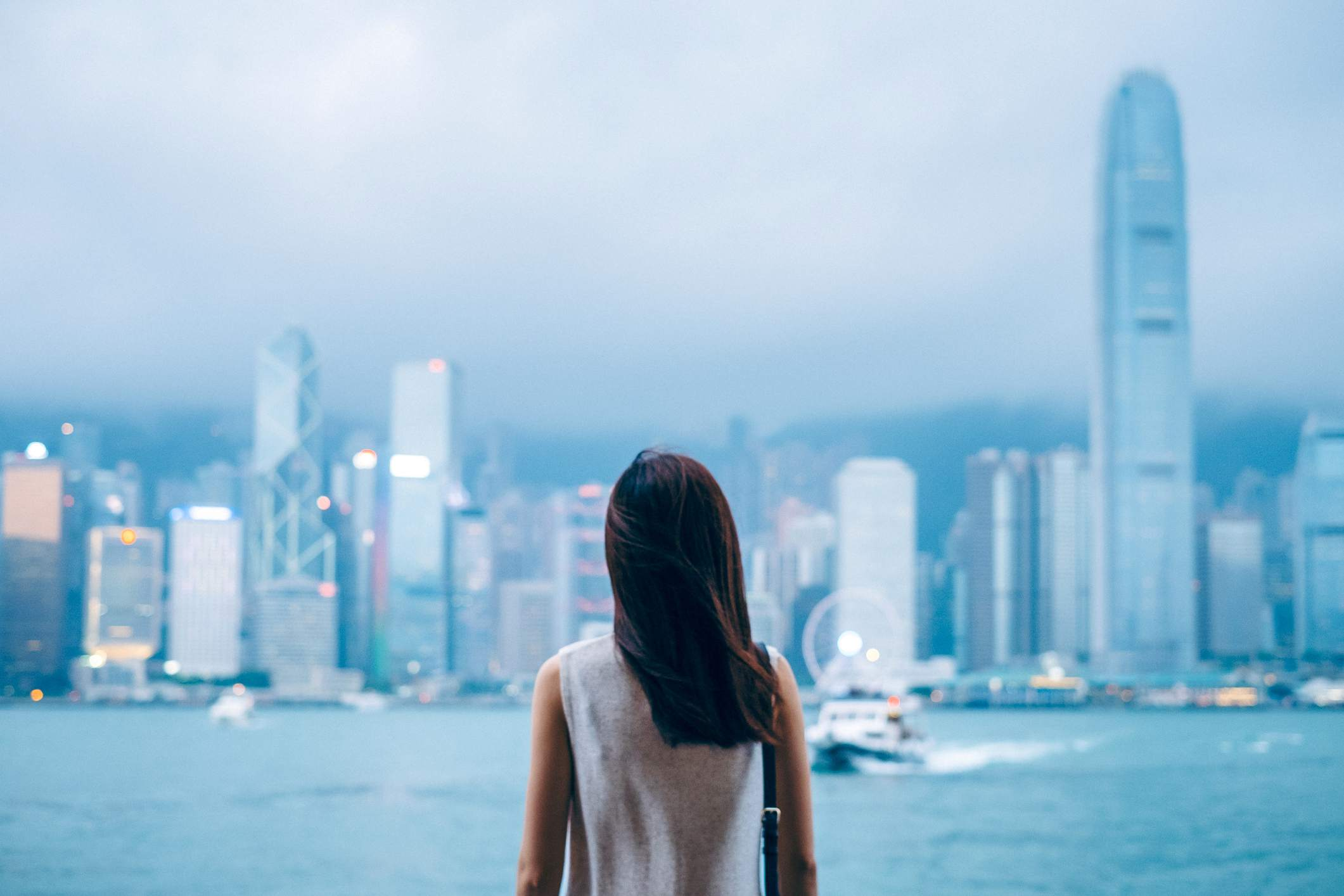Rear view of female traveller enjoys the view at Victoria Harbour and Hong Kong city skyline at dusk