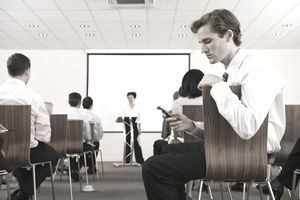Man in training session looking at his cell phone unengaged in the course.