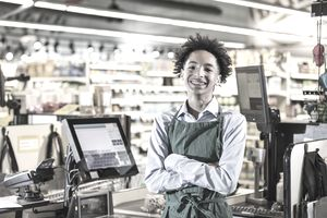 Teenage boy working as supermarket cashier
