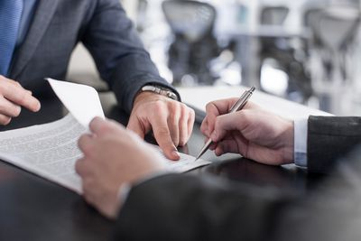 Businessman showing client where to sign nondisclosure agreement document