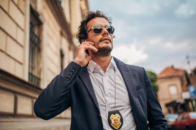 Detective dressed in a shirt and suit jacket and wearing a badge.