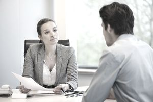 Woman interviewing man at desk