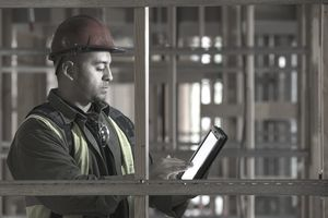 Construction manager reviewing electronic tablet on site