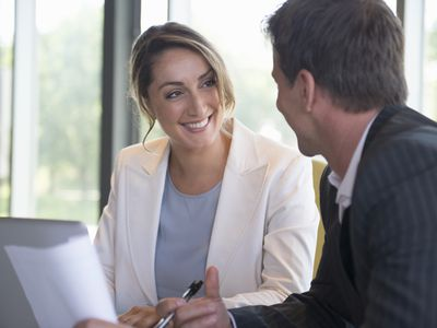 business woman smiling at business man as they work on a project