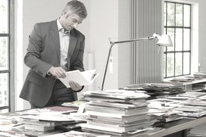 Man standing in front of a table with magazines and books and reading a book