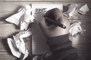 Cropped Hand Of Scriptwriter Writing On Spiral Notebook