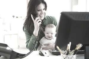 Woman on Phone and at Computer and holding baby while working from home