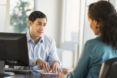 Man and woman talking at desk during job interview