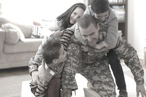 Caucasian children hugging soldier father