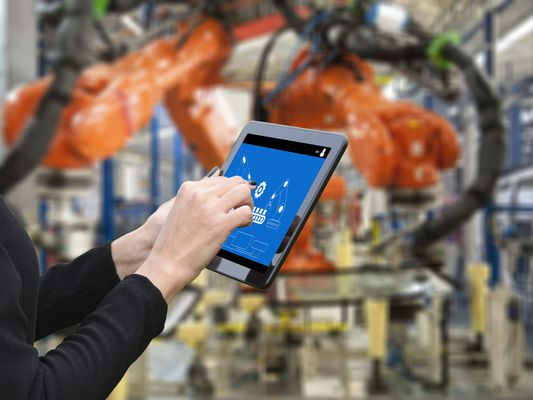 Young female engineer using digital tablet to operate Robotic Arm