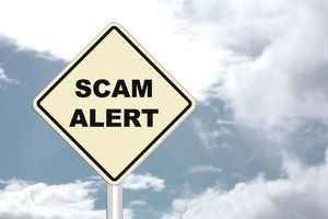 "Road sign that reads ""scam alert"" against a blue sky background."