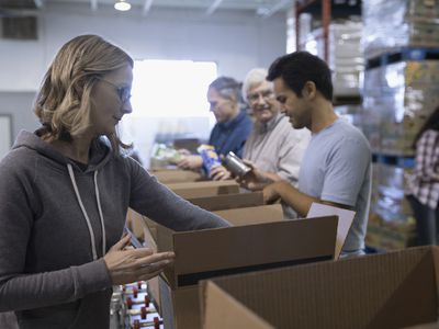 Female volunteer boxing canned food for food drive in warehouse