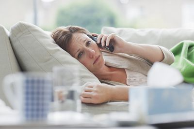 sick woman in bed talking on the phone