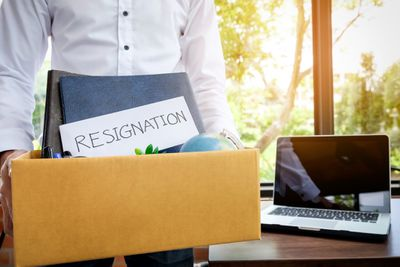 Person carrying a box of belongings with a letter of resignation on the top.