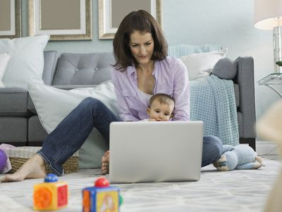 Mother on laptop with baby