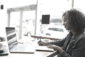 a young woman writing and working on a laptop